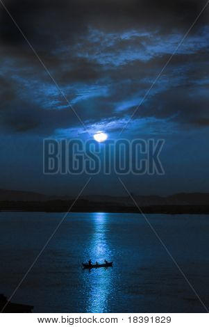 little fishing boot on the river at night lit by the full moon