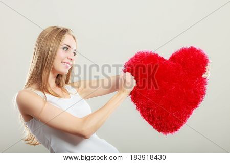 Valentines day love and relationships concept. Blonde long hair young woman holding heart shaped pillow love symbol