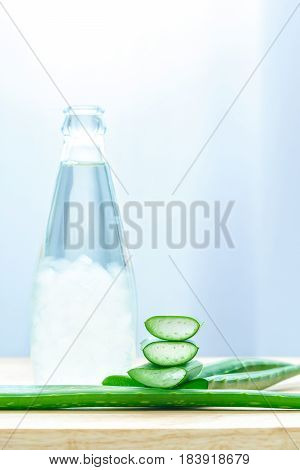 Fresh aloe vera leaves with aloe vera juice in bottle on wooden background