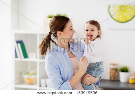 family, teething, motherhood and people concept- happy mother and little baby girl at home kitchen