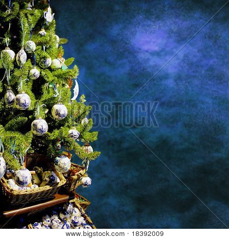 christmas tree with decorations on grungy blue background