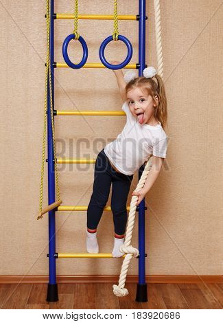 Little girl in sportswear showing tongue and stands on the ladder on the wall bars. The concept of a healthy lifestyle from a young age. Children sport.