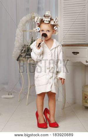 Little girl fashionista. A girl in a curler a robe and red high-heeled shoes is holding a makeup brush. Little coquette. Human emotions.