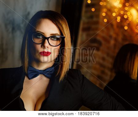 Young attractive girl in a jacket bow tie and glasses. Femme fatale. Evening makeup smokey eye.