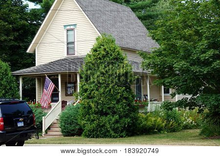 HARBOR SPRINGS, MICHIGAN / UNITED STATES - AUGUST 4, 2016: A single family Victorian home, with a wraparound front porch, flies the American flag on Third Street in Harbor Springs.