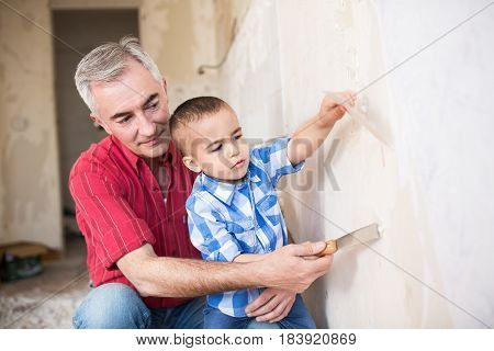 Grandson Is Helping To His Grandfather In Removing Wallpaper