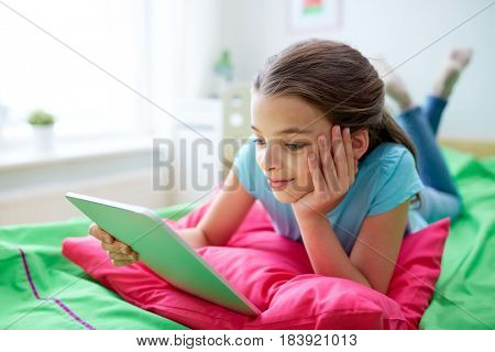 children, technology, people and communication concept - smiling girl with tablet pc lying in bed at home