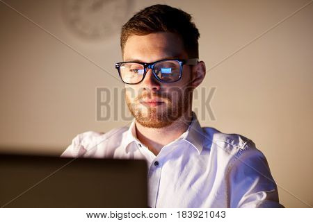 business, overwork, people, deadline and technology concept - businessman in glasses with laptop computer thinking at night office