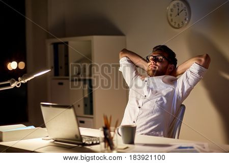 business, overwork, deadline and people concept - tired man with laptop working at night office and stretching
