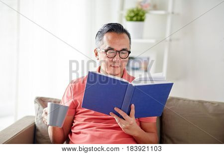 leisure, literature and people concept - man sitting on sofa with mug and reading book at home