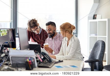 business, startup and people concept - international creative team with papers and tablet pc computer in office