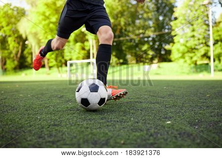 sport, football and people concept - soccer player playing with ball on field