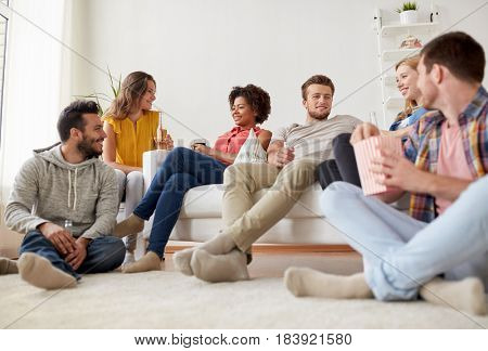 friendship, people and communication concept - happy friends with popcorn and beer talking at home