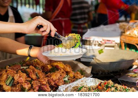 cooking, asian kitchen, people and food sale concept - seller hands with plate of rice serving chilly wok or pilaf dish at street market