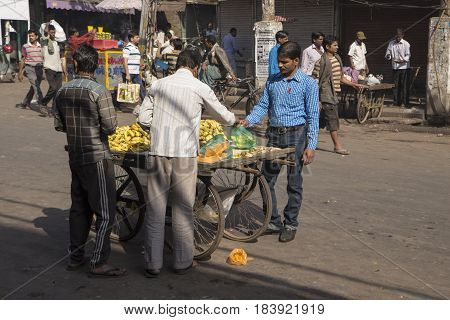 DELHI INDIA - MAR 21 : people buy banana in fruit stall in spice market of delhi on march 21 2015 india. most shop in spice market is close in morning