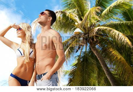 people, travel, tourism and summer holidays concept - happy couple in sunglasses over exotic tropical beach with palm tree background
