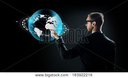 business, future technology, mass media, cyberspace and people - businessman in suit and glasses pointing finger to virtual earth projection over black background