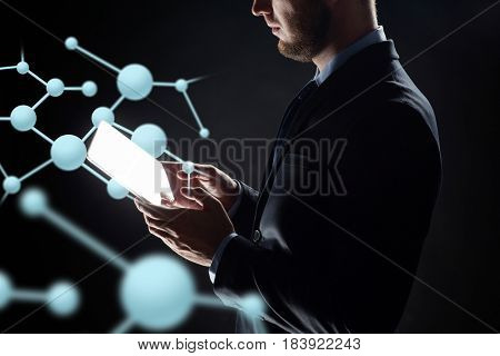 business, people, science, biology and future technology concept - close up of businessman with transparent tablet pc computer and virtual molecule over black background