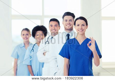 hospital, profession, gesture, people and medicine concept - group of happy doctors showing ok hand sign at hospital