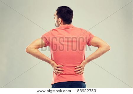 people, healthcare and problem concept - unhappy man suffering from pain in back or reins
