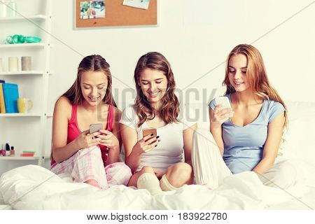 friendship, people, pajama party and technology concept - happy friends or teenage girls with smartphone at home