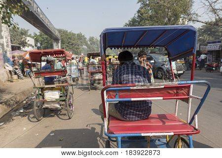 DELHI INDIA - NOV 2 : rickshaw driver waiting for passengers near new delhi railway station. this three wheeler bike is taxi in delhi on november 2 2014 india