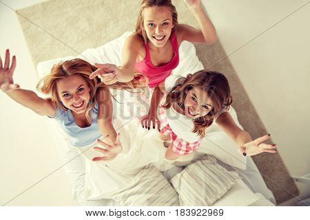 friendship, people and pajama party concept - happy friends or teenage girls having fun, dancing and jumping on bed at home