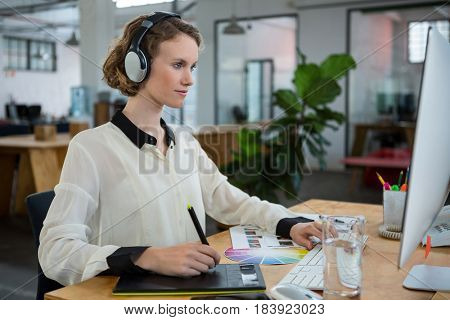 Female graphic designer working at desk in creative office