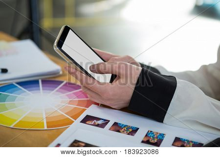 Close-up of female graphic designer using mobile phone at desk in office