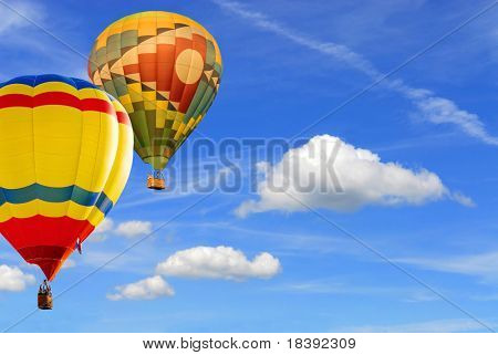 two colorfull hot air balloons floating in blue sky background