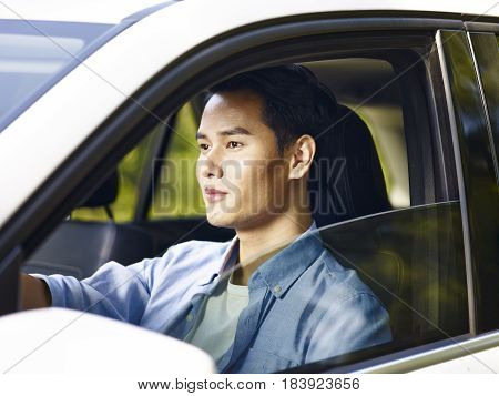 handsome young asian man driving a vehicle.