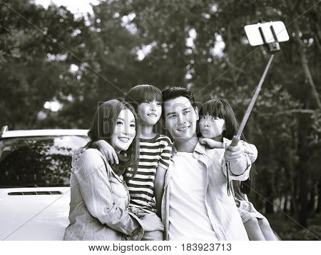 asian family with two children taking a selfie during a trip black and white.