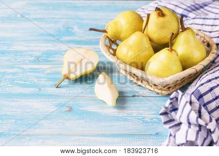 Ripe pears in a basket on a rustic wooden table. The concept of healthy eating with natural products.