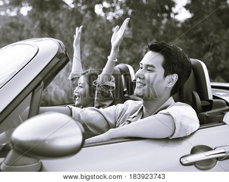 young asian couple riding in a convertible sport car enjoying the cool breeze at sunset black and white.