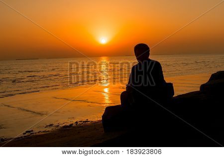 Silhouette of young man standing alone lonly by the sunset light of sea