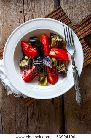 Top View Fresh Summer Vegetables Salad With Eggplants, Tomatoes, Basil Leaves In A White Plate Serve