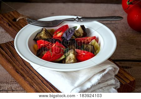 Fresh Summer Vegetables Salad With Eggplants, Tomatoes, Basil Leaves In A White Plate Served On A Wo