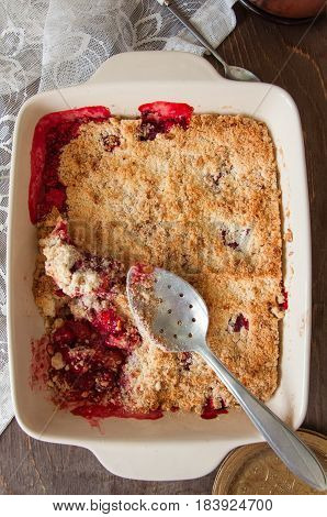 Crumble With Strawberries And Rhubarb In Ceramic Dish On Wooden Table.