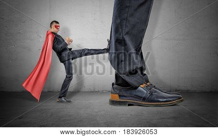 A tiny businessman in a red cape and an eyemask kicking at a retreating giant foot. Market players. Small and big companies. Workplace competition.