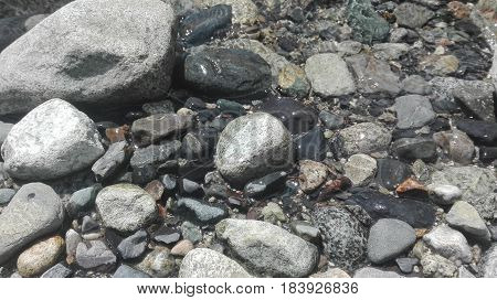 Some Stones under the surface of water, Nature background, River stones in the water of a small and big mountain stream