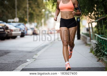 Runner listening to music while jogging on sidewalk, cropped image.