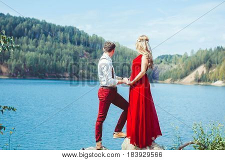 Young couple kissing and rejoices at the lake.