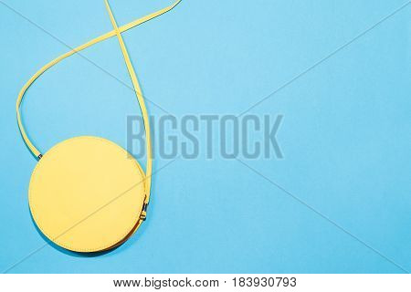 Round yellow cross body bag on a colorful blue background, copy space