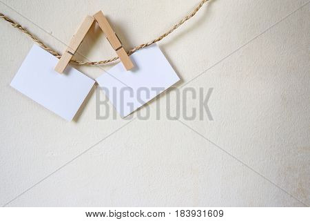 Three Squares Of Blank Paper, Pegged To A String Washing Line, With Wood Plank Fence In The Backgrou