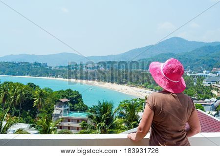 Middle-aged woman enjoying the view over Kata beach from the hotel balcony. Phuket, Thailand