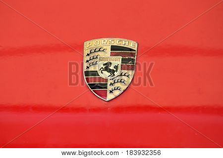 VILNIUS LITHUANIA - APRIL 27: old and scrached Porsche sign close up on the car front on April 27 2017 in Vilnius Lithuania. Ferdinand Porsche founded the company in 1931 with main offices in the centre of Stuttgart
