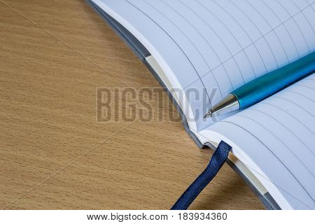 The notebook with pen at wood background