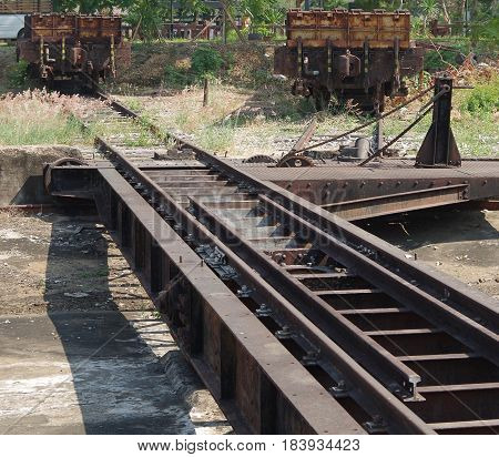 Disused railway turn table and two sidings with wagons.
