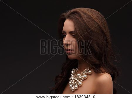 Young Brunette Model Over Dark Background Naked With Necklace Looking Somewhere