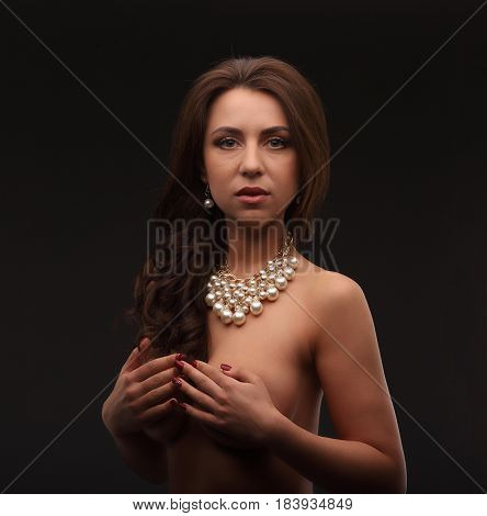 Young Brunette Model Over Dark Background Naked With Necklace Hiding Her Chest And Looking Staight T